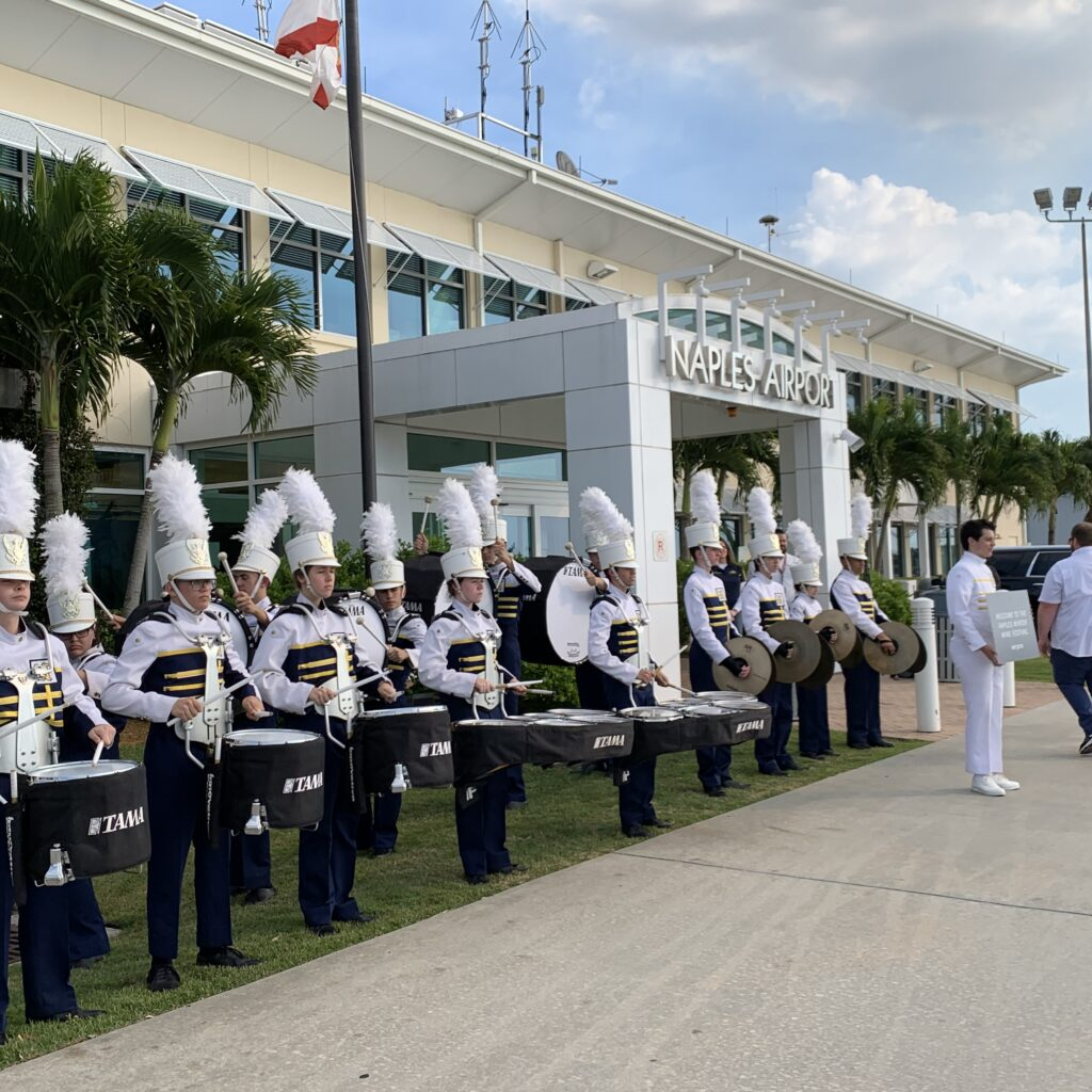 Naples High Band welcoming the winter wine festival attendees at Naples Airport